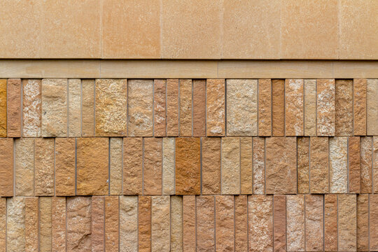 This image shows a modern style rough textured limestone brick wall background with attractive vertical aligned natural kasota stone blocks in varying widths and shades of light brown.