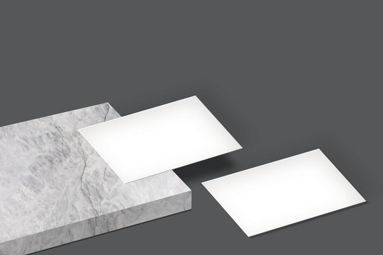 white blank business card mockup on a marble and floor with dark grey background