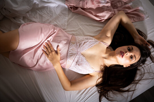 Sexy girl in nightdress sleeping in bed in bedroom at home interior