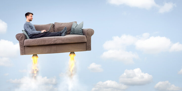 Man flying on a rocket sofa while using a laptop