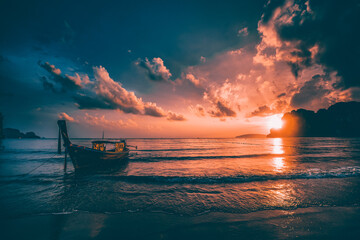 Fototapeta Amazing sunset with longtail boats silhouette at Railay beach, Thailand.