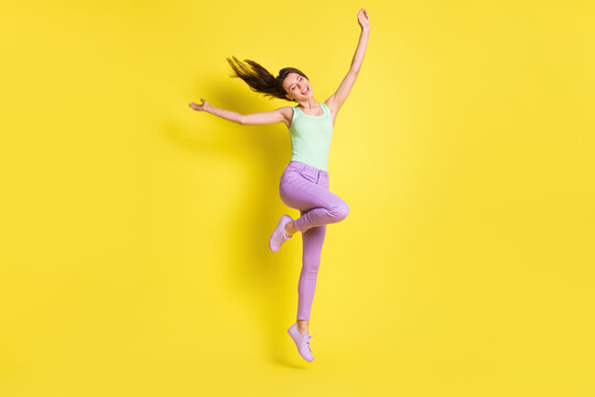 Photo of charming positive lady raise hands jump wear green top pants footwear isolated yellow color background