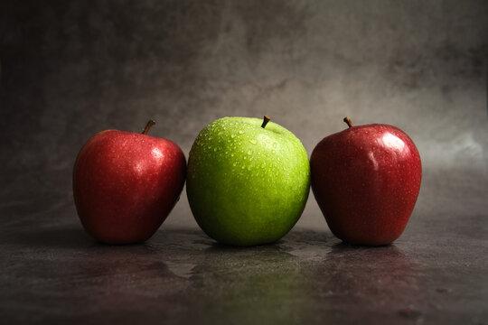 three apples on a dark background