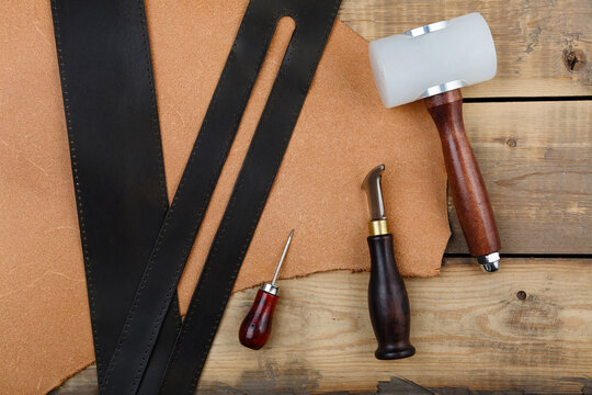 Leatherworker's tools on a wooden workbench.