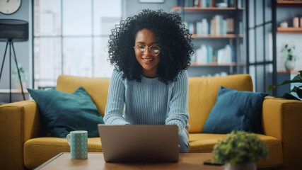 Portrait of a Beautiful Authentic Latina Female in a Stylish Cozy Living Room Using Laptop Computer...