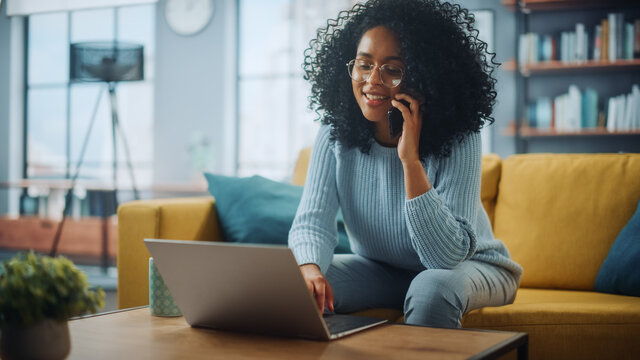 Beautiful Authentic Latina Female in a Stylish Cozy Living Room Using Laptop Computer at Home. She's Answering a Phone Call on Her Smartphone while Browsing the Internet and Checking Social Networks.
