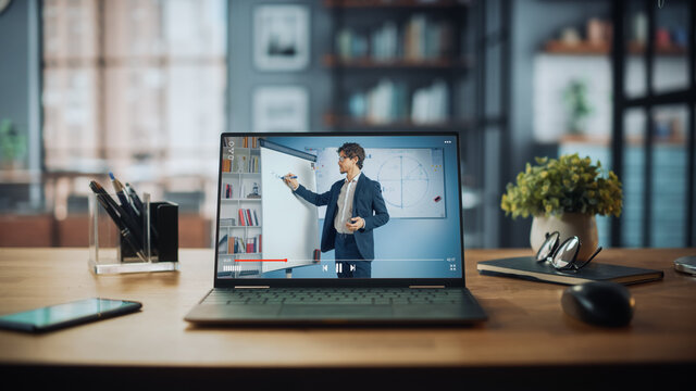Shot of a Laptop Computer Showing Online Lecture with Portrait of a Cute Male Teacher Explaining Math Formulas. It is Standing on the Wooden Desk in Stylish Modern Home Office Studio During Day.