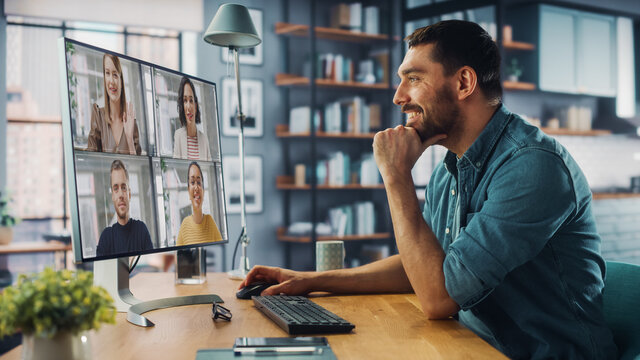 Handsome Caucasian Specialist Making a Video Call on Desktop Computer at Home Living Room while Sitting at Table. Freelancer Working From Home and Talking to Colleagues and Clients Over the Internet.