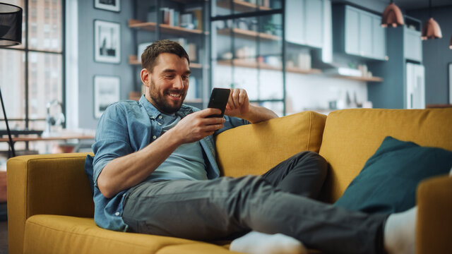 Happy Handsome Caucasian Man Using Smartphone in Cozy Living Room at Home. Man Resting on Comfortable Sofa. He's Browsing the Internet and Checking Videos on Social Networks and Having Fun.