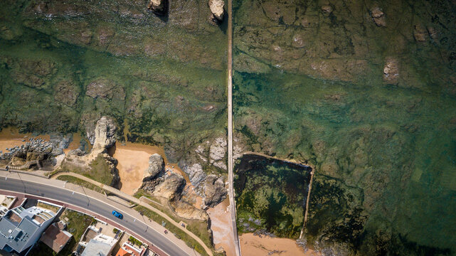Aerial view of a beautiful natural swimming pool built in the ocean through clear water, cliffs and rocks and near coastline road