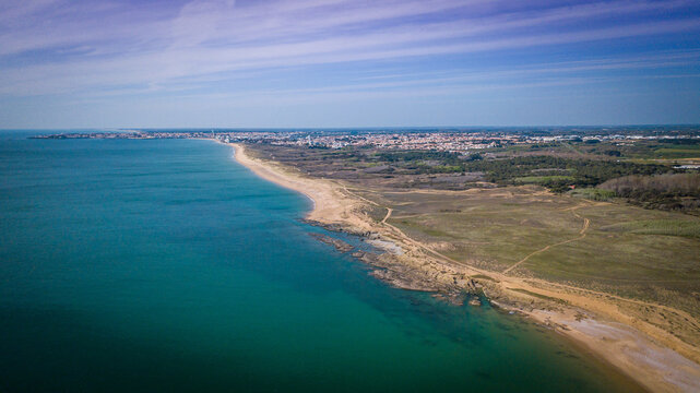 Aerial photography of sunny beaches from above with clear water, sandy dunes, rocks and a town in the background with its harbor