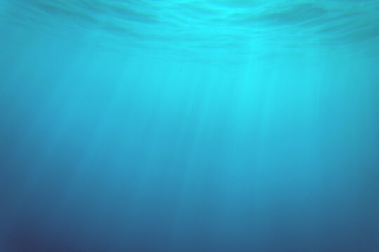 blue ocean surface seen from underwater. waves underwater and rays of sunlight shining through