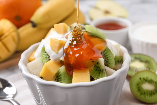 Pouring honey onto delicious fruit salad in bowl on table, closeup