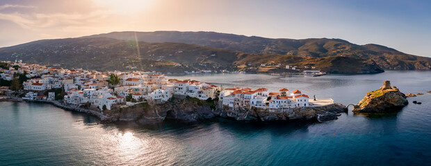 Fototapeta Panoramic view to the town of the Greek island Andros, Aegean Sea, situated on a long stretch into the sea during sunset time