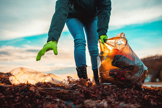 A worker collects garbage on a sea beach. Close-up. The concept of Earth Day. Bottom view