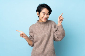 Fototapeta Young Vietnamese woman with short hair over isolated background pointing finger to the laterals and happy obraz