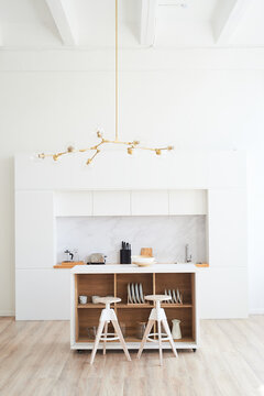 Kitchen in the style of minimalism in white. High countertop with bar stools. A light room in the style of a loft.