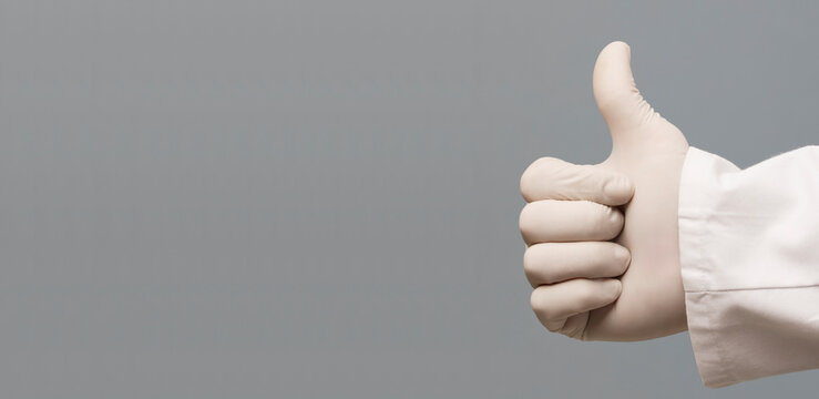 A doctor in blue latex protective glove shows thumbs up as ok sign, isolated on gray background