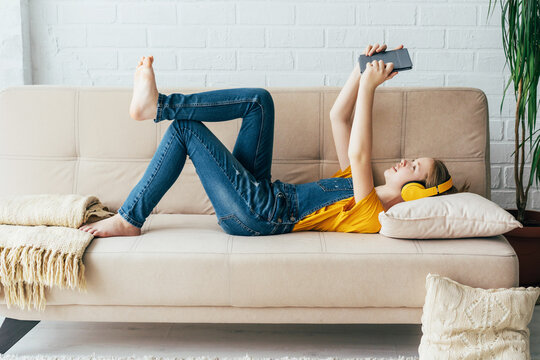 Teenage girl in denim overalls relaxes in pleasure on the couch with an electronic tablet. The child communicates in video chat with wireless Internet devices.