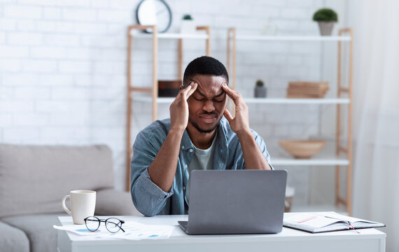 African American Businessman Having Headache Sitting At Laptop Indoor