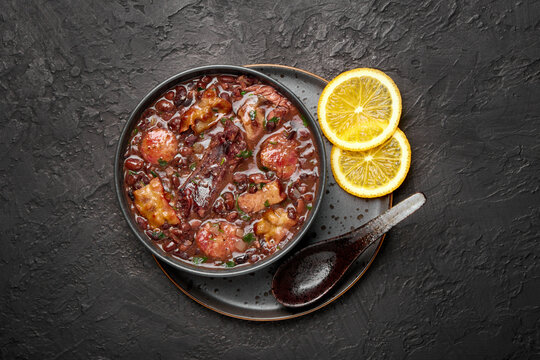 Feijoada in black bowl on dark slate table top. Brazilian and portuguese cuisines traditional beans meat stew