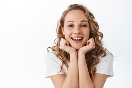 Beauty and fashion. Attractive lady with blond curly hair, leaning head on hands and smiling, showing beautiful natural facial skin without make up, standing over white background