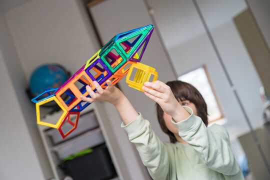 Child plays with a magnetic constructor  in a room. Boy building a rocket from blocks. Kid playing with colorful toys.