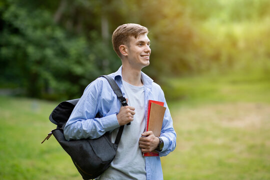 Outdoor portrait of attractive teen student guy with backpack and workbooks