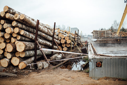 warehouse of a woodworking plant. the bundles of logs are stored and ready for transportation. a lot of processed smooth wooden bars