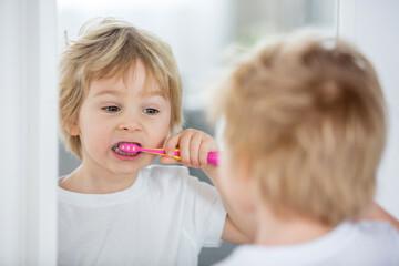 Fototapeta Cute toddler child, blond boy, brushing his teeth at home