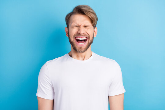 Photo portrait of young man in casual t-shirt laughing with opened mouth isolated bright blue color background