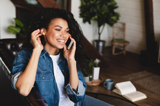 African-american young woman talking on phone in her cosy house. Businesswoman working from home office and using cell phone. Beautiful afro american woman sitting at the desk in a home office.