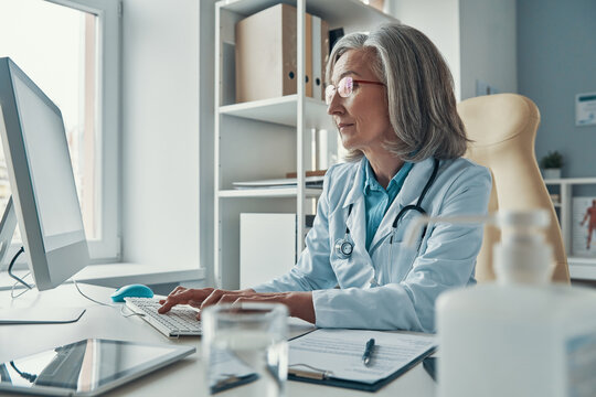 Serious mature female doctor in white lab coat working using computer while sitting in her office