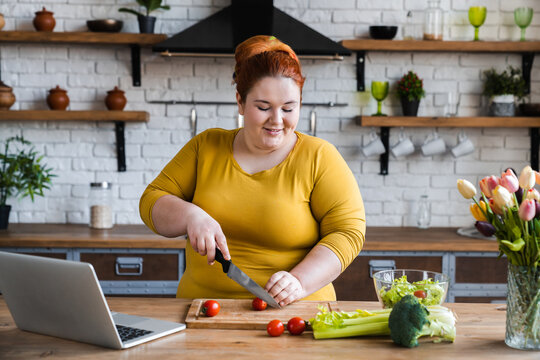 Plus size , fat caucasian woman learning to make salad and healthy food from social media,Social distancing, stay at home concept