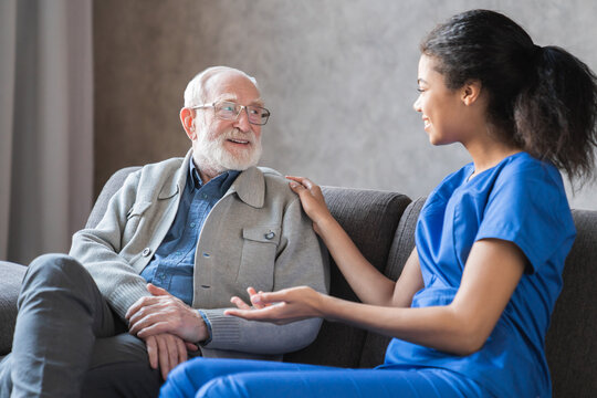 Caring african-american nurse talks to old elderly senior patient holds his hand sit in living room at homecare visit provide psychological support listen complains showing empathy encouraging.