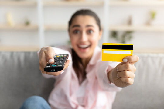 Excited woman holding remote control and debit credit card