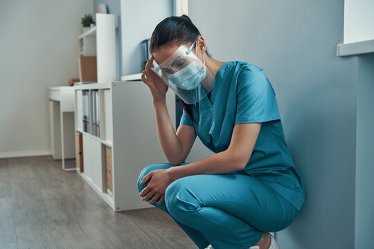 Tired young female nurse in protective workwear