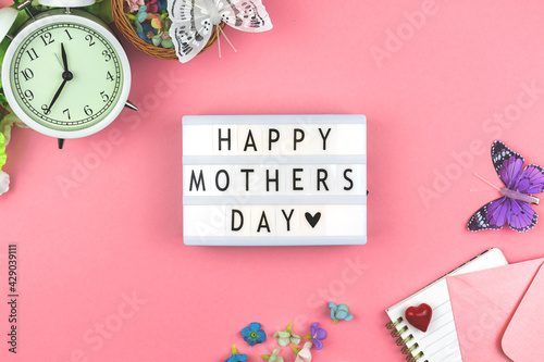 Happy Mother's Day text background, spring workspacewith flowers and butterflies, flat lay and top view with lightbox