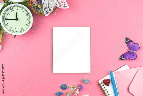 Spring greeting card mockup, mother's day and holiday blank white paper, feminine workspace with pink background, alarm clock, flowers and butterflies, copy space