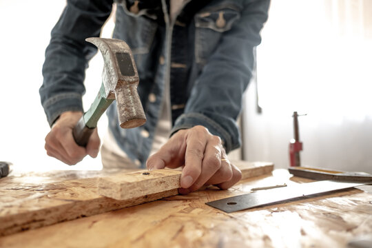 Male carpenter builderworking with wooden board in the workshop to decorate the woodwork.