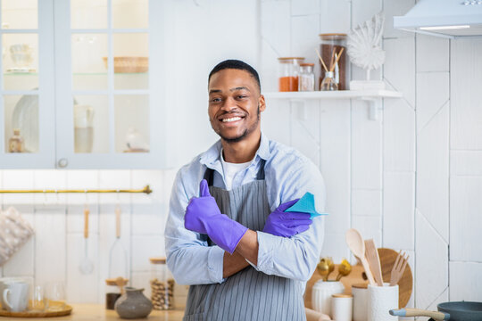 Handsome young black man in rubber gloves smiling at camera and showing thumb up gesture in kitchen