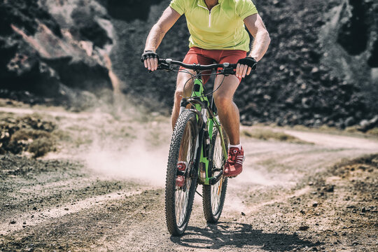 Mountain bike MTB biking athlete man in mountains landscape jumping riding bicycle. Professional bicycle rider body crop training outdoors. Sport and fitness background.