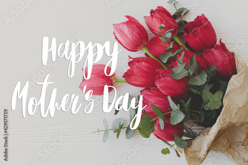 Happy mother's day greeting card. Happy mother's day text and red tulips bouquet in craft paper on rustic white wood. Stylish floral greetings. Handwritten lettering. Mothers day