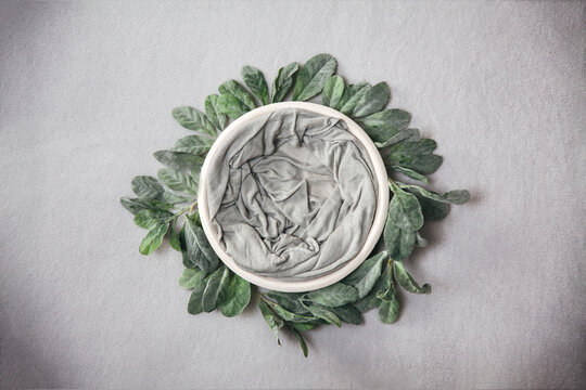 Neutral newbsorn backdrop - cream bowl with sage green leaves wreath on light grey background