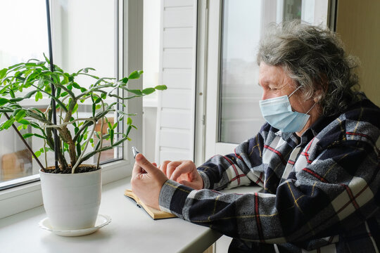 An elderly man in a protective mask on self-isolation reads the news at home, sitting by the window. Self-isolation in quarantine due to the global coronavirus pandemic