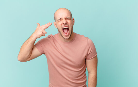 bald man looking unhappy and stressed, suicide gesture making gun sign with hand, pointing to head