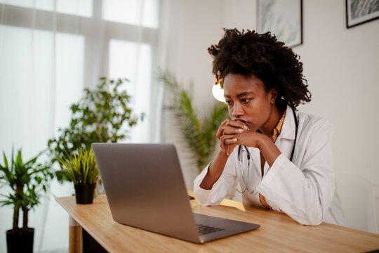 Worried black female doctor working on computer at her desk.