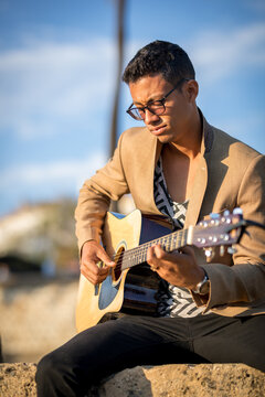Portrait of Latin man sitting and playing guitar on the street during sunset