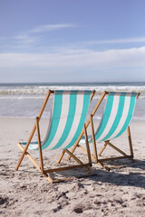 View of two deck chairs on the beach with sea waves