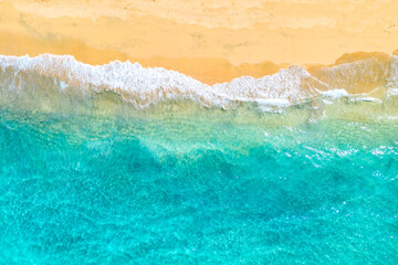 Vacation travel background. Top view aerial drone photo of ocean seashore with beautiful turquoise water and foam sea waves. Caribbean resort.